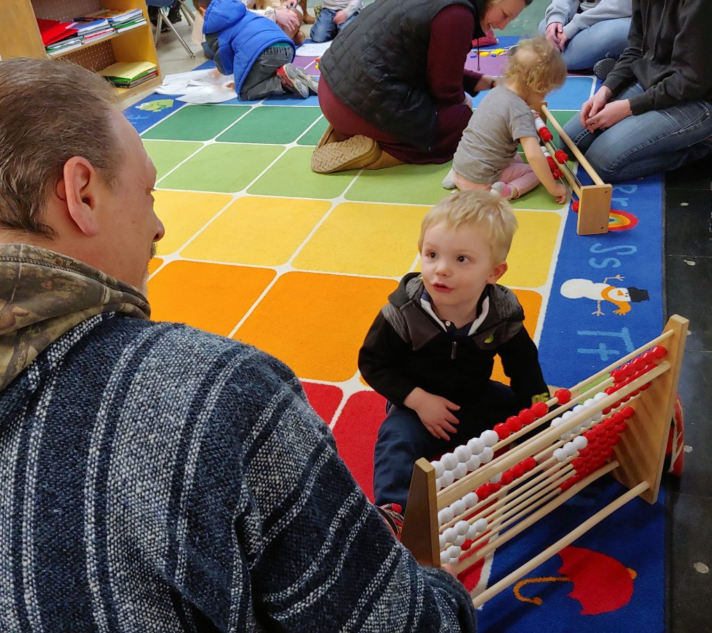 boy moves beads on abacus