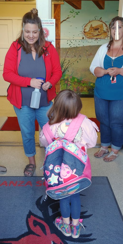 Bonanza Elementary School secretary Caitlin Leslie offers hand sanitizer to a first grader before she heads to class.
