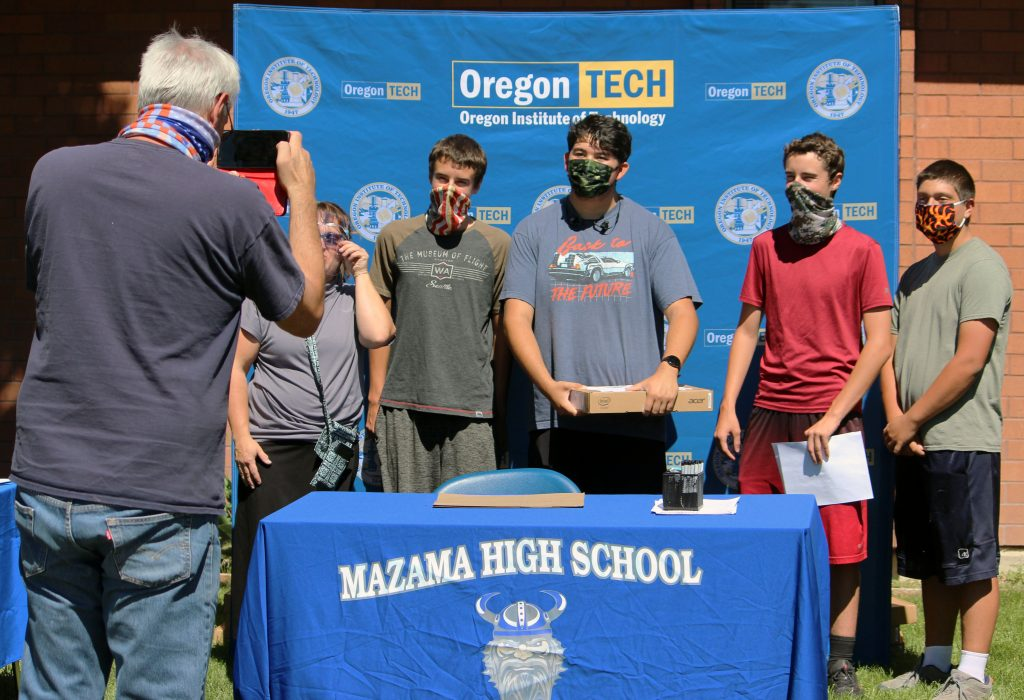 A parent takes a photo while four friends – Matthew Elfbrandt, Diego Diaz, Mark Elfbrandt, and Thackery Moreland– pose with STEM&M advisor Laura Nickerson Tuesday after signing their contracts.