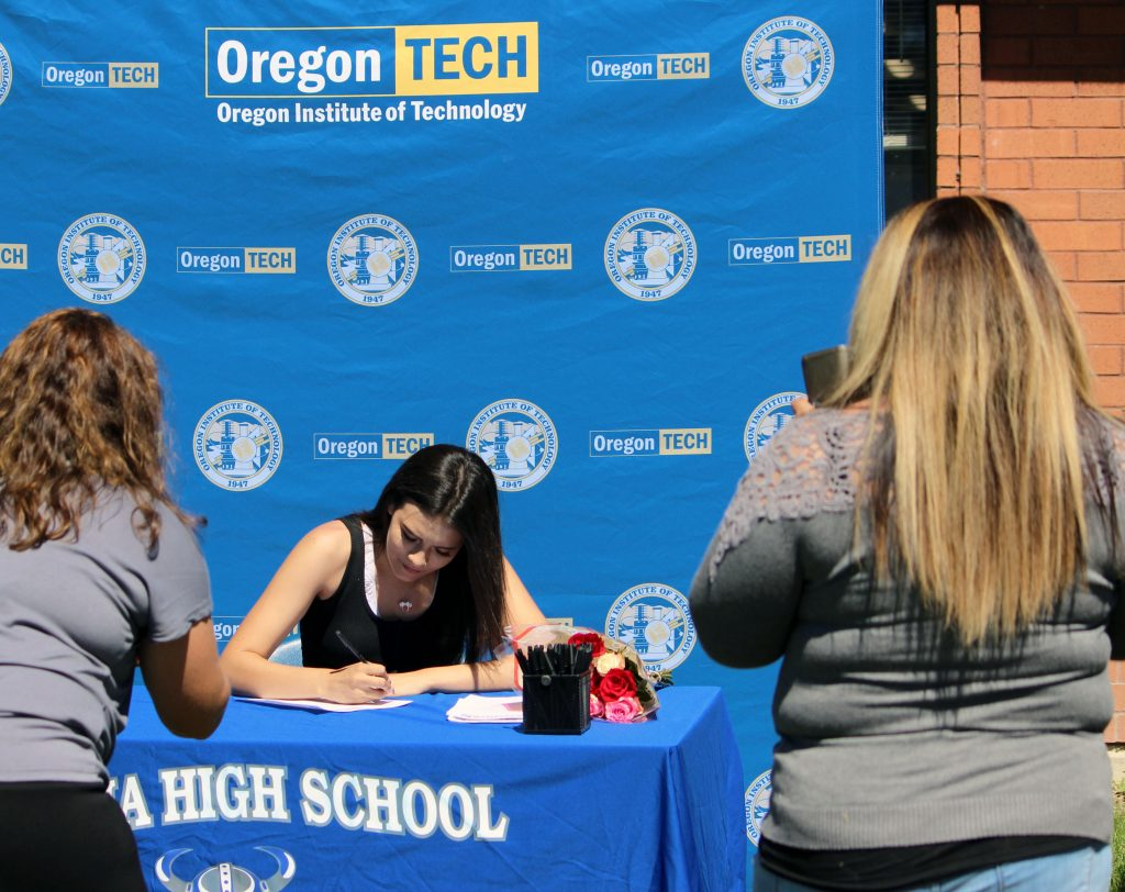 Mazama sophomore Kristalina Derry signs her STEM&M contact while advisor Laura Nickerson, left, and a parent takes photos.