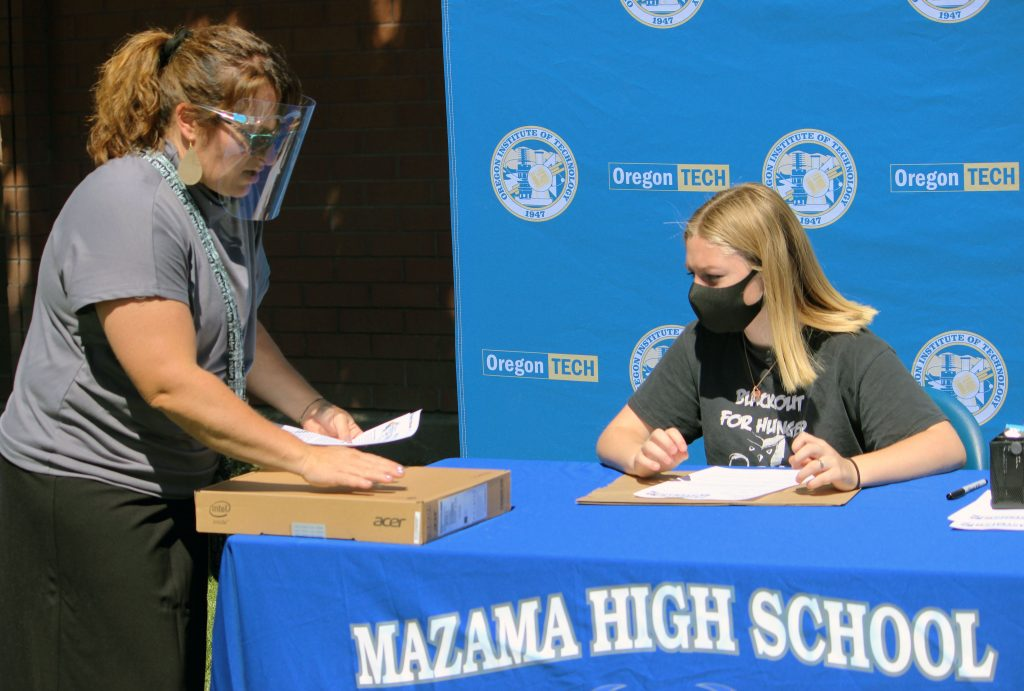 After signing her contract, Mazama sophomore Jordin Cantamessa receives her Chromebook from STEM&M advisor Laura Nickerson.